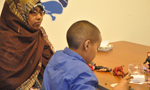 Somali mother watches child studying