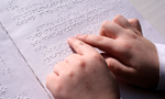 A child's hands reading Braille