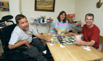 Man with disabilities playing a board game at a group residence